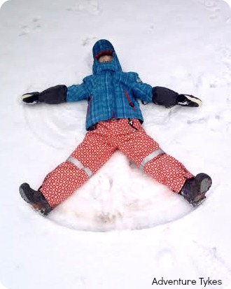 Toddler making snow angels