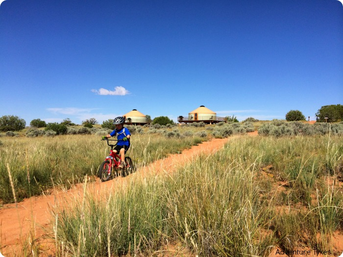 Child mountain biking by yurts