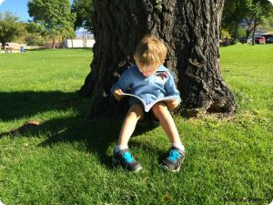 child reading at the park