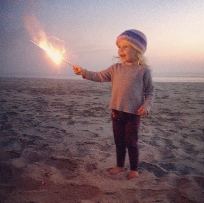 Toddler with a sparkler on the beach